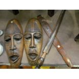 A pair of African tourist ware masks and two paddles,