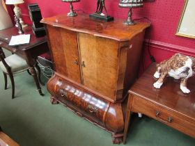 A French style television cabinet of bombe chest form, twin folding doors over base fall-flap,