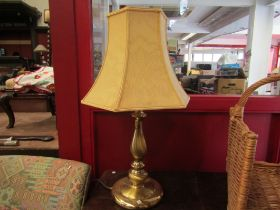 A brass table lamp with peach shade