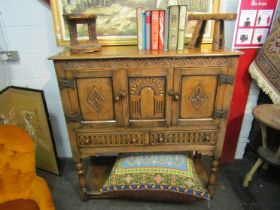 An Old Charm style oak cupboard with carved doors and two frieze drawer,