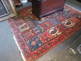 A Persian rug in reds, blues and ochre,