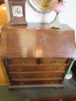 A mahogany bureau, reeded columns, two over three drawer base, carved bracket feet,