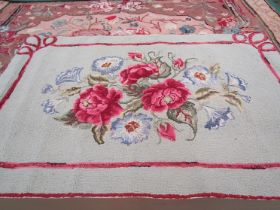 An American 1930's-40's small rosey floral hooked rug with grey, green ground,