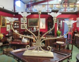 A cream five sconce candlestand with glass drip trays