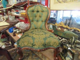 A mid Victorian carved walnut button-back armchair,