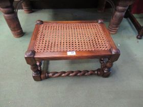 An Edwardian bergère stool, the caned seat on turned legs joined by barley-twist stretchers,