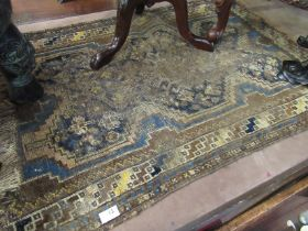 An Eastern blue and brown ground rug, heavily worn,