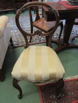 A pair of Victorian walnut balloon back chairs with carved decoration on scroll foot cabriole fore