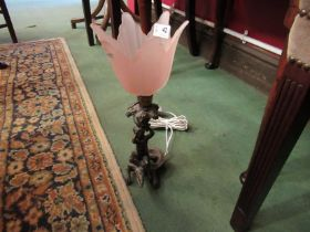An ornate bronzed table lamp in the form of a putti seated on alligator under branching grapevines