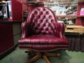 A Georgian style red leather button back library swivel desk armchair with brass stud decoration