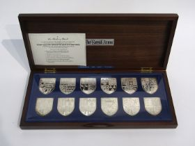 """The Danbury Mint """"The Royal Arms"""" collection of 12 silver ingots,"""