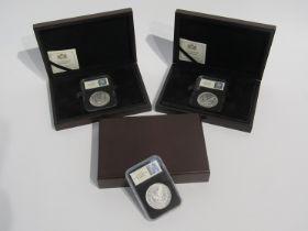 Three US silver Morgan dollars, Philadelphia, cased and boxed,