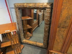 A large gilt metal feature mirror with bevelled glass,