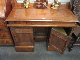 An elm pedestal clerks desk the sloped top over a heavily carved kneehole base,