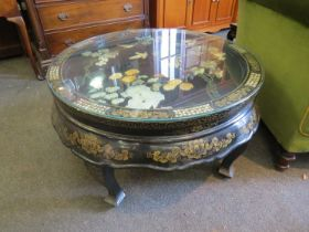A 20th Century oriental lacqered circular coffee table with mother of pearl and gilt border,
