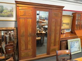 A Victorian walnut wardrobe, central mirrored door flanked by two further burr wood panelled doors.