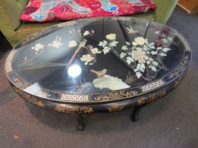 A 20th Century oriental lacuered oval coffee table with mother of pearl and gilt border,