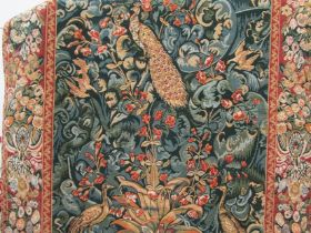 A modern machine woven wall hanging tapestry depicting peacocks in a stylized naturalistic setting,