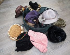 A green hat box containing a quantity of assorted fashion hats