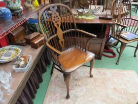 A pair of elm stick and wheel back elbow chairs with crinoline stretchers on pad front feet