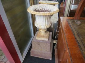 A 19th Century cast egg and dart urn on associated stand,