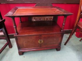 A Chinese style mahogany two tier cabinet/occasional table the dished top on turned supports over a