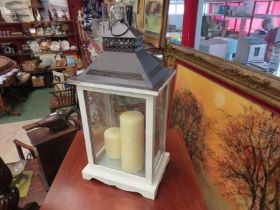 A painted wooden lantern, pierced metal top with candles,