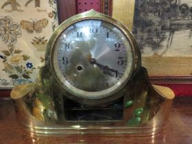 A brass cased mantel clock, engraved decoration on front.