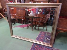 A brushed gilt wall mirror with bevelled glass,