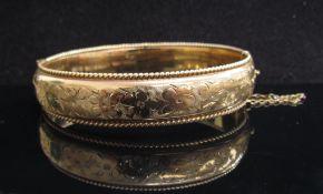 A 9ct gold floral engraved stiff hinge bangle, 6cm x 5.5cm, 20.5g