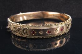 A 9ct gold stiff hinge bangle with ruby and diamond chips, dented, 13.4g