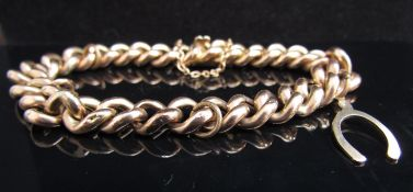 A hollow link bracelet stamped 15ct with 9ct gold wishbone charm, 17.2g