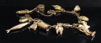 A 9ct gold charm bracelet hung with various 9ct gold charms including squirrel, teddy bear,