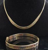 A 9ct three tone gold stiff hinge bangle and matching necklace, 29.8g