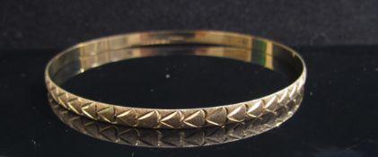 A 9ct gold engraved bangle, 6.5cm diameter, 5.5g