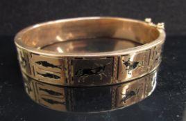 A rose gold stiff hinge bangle with panelled design of Zodiac symbols, unmarked, 22g