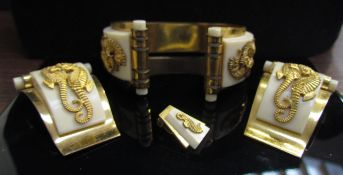 A 1930's Jean Painleve gilt metal bangle with seahorse motif, matching dress clips and one earring