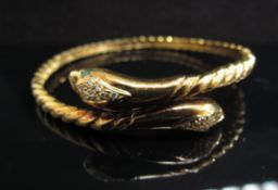 A gold hinged snake bangle with emerald set eyes and diamond set head, stamped 14k, 22g