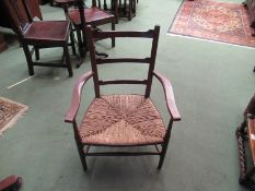 A pair of 19th Century North West Country oak and ash ladder-back elbow chairs with rush seats and
