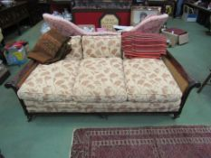 A late Victorian mahogany three seater bergère sofa with carved acanthus leaf decoration on turned