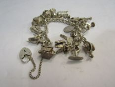 A silver charm bracelet with multiple charms including Poodle, wagon and dog in kennel, 91.