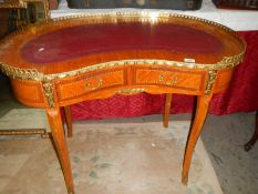 A kidney shaped ormolu mounted writing desk with leather inset top.