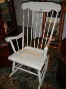A white painted rocking chair.