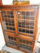 A four door oak lead glazed cabinet.