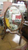An oval mahogany framed toilet mirror.