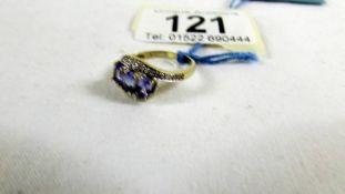 A Tanzanite and diamond ring in a twist design, size L.