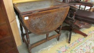 A good carved oak drop leaf table.