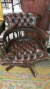 A superb quality deep buttoned brown leather captain's chair.