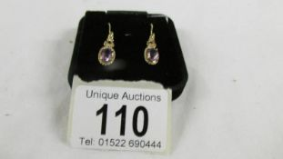A pair of amethyst ear pendants in 9ct gold with shepherds hook fittings.
