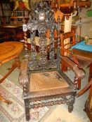 A pair of elaborately carved oak hall chairs (cane seats need replacing).